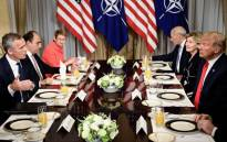 NATO Secretary General Jens Stoltenberg (L) and US President Donald Trump (R) and staff speak at a breakfast meeting at the US chief of mission's residence in Brussels on 11 July 2018, ahead of a NATO (North Atlantic Treaty Organisation) summit. Picture: AFP.