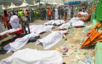 Saudi emergency personnel and haj pilgrims stand near bodies covered in sheets at the site where at least hundred were killed and wounded in a stampede in Mina, near the holy city of Mecca, at the annual haj in Saudi Arabia on 24 September 2015. Picture: AFP.