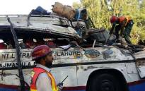 Pakistani rescue officials gather around the wreckage of a passenger bus after an accident in Khanpur, some 800 kilometres south of Islamabad. Picture: AFP.