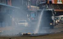 Riot police use a water cannon as they patrol the streets to break up barricades set up by the opposition led by the Movement for Democratic Change on 12 July 2017 in Harare, Zimbabwe. Picture: AFP.