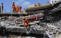 Members of the National Disaster Response Force (NDRF), along with local police, search for victims after an under construction building collapsed in the village of Shah Beri village in Greater Noida, a satellite town east of the Indian capital, in Uttar Pradesh on 18 July, 2018. Picture: AFP.