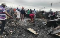 Dunoon residents clear the piece of land where their houses once stood following a fire on 13 March 2018. Picture: Shamiela Fisher/EWN.