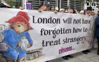 Demonstrators wearing Paddington Bear masks hold up a banner as they protest outside the Home Office in London in October 2016. Picture: AFP.