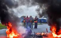 Trade union members block a traffic circle on 25 September 2017 in Donges, western France, to protest against the government's labour law. Picture: AFP