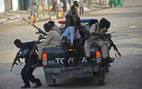 FILE: Somali government police officers arrive to secure the area of a suicide car bombing near the SYL hotel in Mogadishu on 22 January, 2015. Picture: AFP.