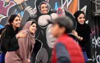 FILE: Saudi girls pose for a group picture as one stands behind a frame depicting King Kong, while attending the first ever Comic-Con Arabia event held in the capital Riyadh on 25 November 2017. Picture: AFP.