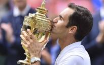 Switzerland's Roger Federer kisses the winner's trophy after beating Croatia's Marin Cilic in their men's singles final match, during the presentation on the last day of the 2017 Wimbledon Championships on 16 July 2017. Picture: AFP.