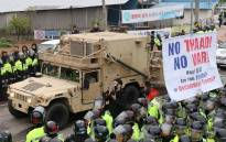 Protesters and police stand by as trailers carrying US THAAD missile defence equipment enter a deployment site in Seongju, early on 26 April, 2017. Picture: AFP.