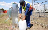 A City of Cape Town official show the media how the Day Zero Water Station works. Picture: Bertram Malgas