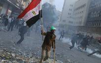 Demonstrators dodge tear gas during clashes in a Cairo street on November 22, 2011. Picture: AFP