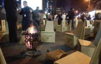 CEOs will sit around these fires and use their cardboards chairs as beds for The 702 Sun International CEO Sleepout in Sandton. Picture: Kgothatso Mogale/EWN.