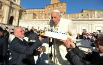 Pope Francis blows out the candles of a birthday cake to celebrate his 78th birthday during a general audience at the Vatican on 17 December 2014. Picture: AFP,
