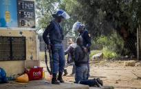 FILE: Police question a man outside a looted liquor store in Coligny in the North West after protests in the town on 25 April 2017 over the death of a young boy. Picture: Reinart Toerien/EWN