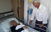 This handout picture taken on March 4, 2017, and obtained on March 5, 2017 from the Ahmed Kathrada Foundation shows ANC stalwart Ahmed Kathrada (L) recovering after a surgery in a hospital in Johannesburg, being comforted by fellow Robben Island former prisoner, Laloo Chiba. Picture: AFP