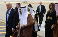US President Donald Trump (L), accompanied by his wife Melania Trump, walks with Saudi King Salman bin Abdulaziz al-Saud (C) upon arrival at King Khalid International Airport in Riyadh on 20 May 2017. Picture: AFP.