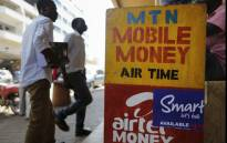 A photograph made available on 22 February 2016 shows people walking in front of a mobile money transfer shop for MTN and Airtel lines in Kampala, Uganda, 17 February 2016. EPA/Dai Kurokawa.