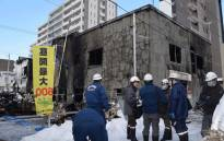 Policemen and firefighters check the ruins of a fire at a residence for elderly people in Sapporo, northern Japan, on 1 February, 2018. Picture: AFP