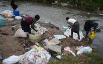 A group of women wash used plastic bags for re-use at the shores of a river on June 24, 2014 in Nairobi. Picture: AFP