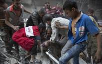 FILE: Syrians pull the body of a from the rubble of a building following government forces air strikes in the rebel held neighbourhood of Al-Shaar in Aleppo. Picture: AFP.