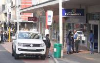 Police stand outside the Cash Crusaders that was robbed earlier in the day. Two armed men fled the scene with a cellphone after forcing staff into the back of the store. Picture: Bertram Malgas/EWN