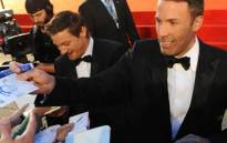 US film director Ben Affleck (R) and actor Jeremy Renner sign autographs. Picture: AFP.