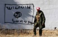 FILE: A Kurdish fighter walks by a wall bearing a drawing of the flag of the Islamic State (IS) group in the northern Iraqi town of Sinjar, in the Nineveh Province, on 13 November 2015. Picture: AFP.
