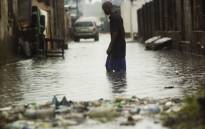 A man walks through water after rains flooded the streets in a neighborhood of Kinshasa, Congo. Picture: AFP.
