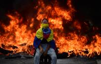 A Venezuelan opposition activist is backdropped by a burning barricade during a demonstration against President Nicolas Maduro in Caracas, on 24 April, 2017. Picture: AFP