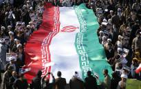 Pro-government demonstrators wave their national flag during a march in Iran's holy city of Qom, some 130km south of Tehran, on 3 January, 2018. Picture: AFP