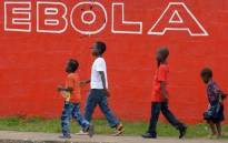 A file photo taken on 31 August, 2014 shows children walking past a slogan painted on a wall reading 'Ebola' in Monrovia. Picture: AFP.