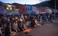 Men pray after hundreds of people celebrated Iftar, which is the evening meal which breaks the daily Ramadan fast for Muslim people, in the middle of Wale Street in Bo-Kaap, on 1 June 2018. Picture: AFP.