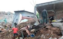 Sri Lankan residents walk through damaged homes at the site of a collapsed garbage dump in Colombo on April 15, 2017. Picture: AFP