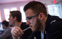 FILE: Kyle Stamm, of New York, vapes, or smokes an electronic cigarette, at Henley Vaporium on April 29, 2014 in New York City. Picture: AFP.