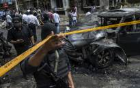 Egyptian security forces stand guard at the site of a bomb attack that targeted the convoy of Egyptian state prosecutor, Hisham Barakat, who died hours after the powerful explosion hit his convoy, in the capital Cairo on 29 June 2015. Picture: AFP.