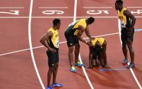Jamaica's Usain Bolt (2R) reacts after injuring himself as team-mates try to help him during the final of the men's 4x100m relay athletics event at the 2017 IAAF World Championships at the London Stadium in London on 12 August 2017. Picture: AFP.