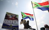 A poster calling for protest action against the violence in Myanmar held up next the South African Flag during a MJC march. Picture: Bertram Malgas/EWN