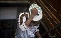 Convicted murderer Mthinta Bhengu holds his hat over his face as he enters the dock ahead of sentencing in the murder case of Emmanuel Sithole in the Johannesburg Magistrate's court. Picture: Reinart Toerien/EWN.
