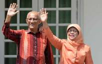 Singapore's new President Halimah Yacob (R) waves to supporters with her husband Mohammed Abdullah Alhabshee as they arrive at the nomination centre in Singapore on 13 September 2017. Picture: AFP.