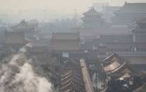 Steam rises behind a wall of the Forbidden City, once the home of Chinas emperors, on a polluted day in Beijing on 19 December 2015. Picture: AFP.