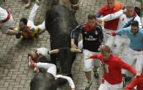 FILE: Participants run beside Fuente Ymbro's fighting bulls during the fourth bull run of the San Fermin festival on 10 July 2017. Picture: AFP.