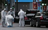 Forensic experts of the police search for evidence in and around the car of Greek former prime minister Lucas Papademos in Athens on May 25, 2017, after Papademos was hurt when an explosive device went off inside his car. Picture: AFP.