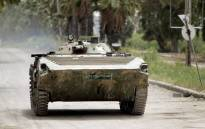 FILE: A Syrian army tank patrols an area in the district of Al-Waar in the flashpoint city of Homs. Picture: AFP.