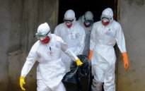 FILE: Medical workers of the Liberian Red Cross, wearing a protective suit, carry the body of a victim of the Ebola virus in a bag on 4 September, 2014 in the small city of Banjol, 30 kilometres of Monrovia. Picture: AFP