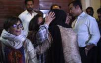 A Pakistani woman hugs a relative of Junaid Jamshed, a former Pakistani pop star turned evangelical Muslim, at his house in Karachi on 7 December  2016, after his death in plane crash. Picture: AFP.