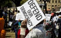 A member of the public, unhappy with President Jacob Zuma's recent Cabinet reshuffle, holds up a placard at a public gathering organised by the Save SA campaign outside National Treasury in Pretoria on 3 April 2017. Picture: Reinart Toerien/EWN.
