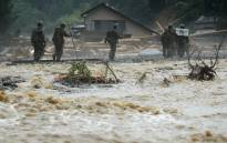 Defence forces soldiers walk beside a river during a search operation for missing poeple in a flooded area in Asakura on 9 July 2017. Picture: AFP.