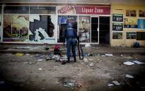 A police officer searches the area outside a looted liquor store in Coligny in the North West on 25 April 2017 after protests in the town over the death of a young boy. Picture: Reinart Toerien/EWN