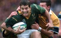 Joost Van Der Westhuizen (front) is tackled by Australian fullback Matthew Burke (R) during the Rugby World Cup semi-final match between Australia and South Africa at Twickenham stadium 30 October 1999. Picture: AFP.