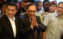 Jailed former opposition leader and current federal opposition leader Anwar Ibrahim (C) gestures as he speaks to the media after returning to his home following his release from hospital in Kuala Lumpur on 16 May, 2018. Picture: AFP