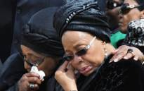Nelson Mandela's wife Graça Machel (R) and ex-wife Winnie Madikizela-Mandela leaving Mthatha Airport after the arrival of his body, 14 December 2013. Picture: GCIS.